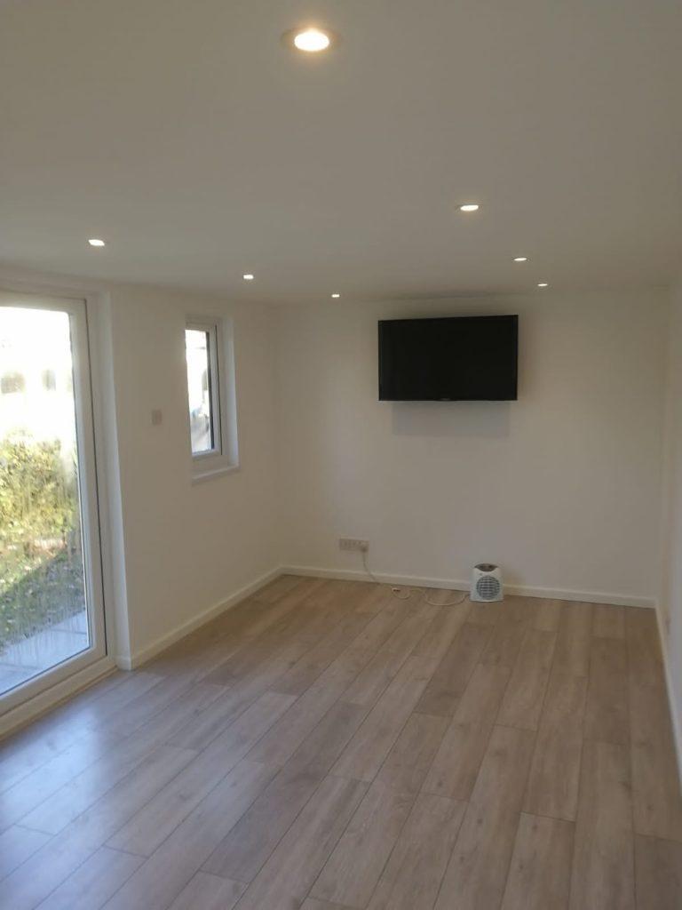 Garden room with TV and wooden floor