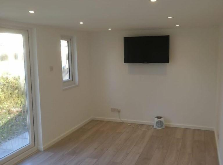 TV mounted on wall in newly built garden room
