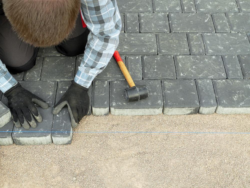 Man building a driveway with grey bricks